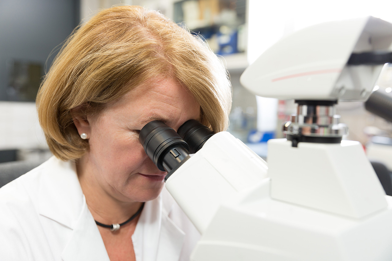 A woman researcher looking into a microscope